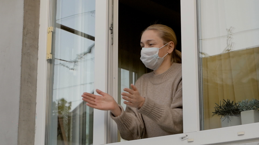 Woman in medical mask claps his hands looking out the open window | Shutterstock HD Video #1051423612