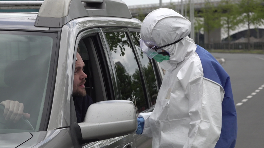Health care worker in protective hazmat suit (and gloves, mask, and glasses) takes sample from coronavirus Covid-19 patient, through window of an SUV in a drive thru test clinic  | Shutterstock HD Video #1051433815