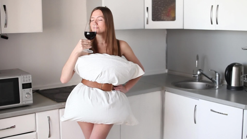 Beautiful girl in a dress of white pillows on the background of the kitchen drinks red wine from a glass. Crazy quarantine concept.   Shutterstock HD Video #1051438045