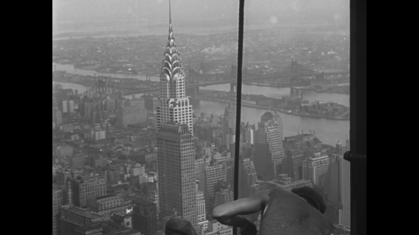 CIRCA 1930 - Construction workers working on the Empire State Building have a good view of the Chrysler Building.