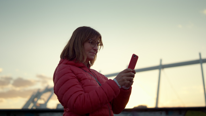 Portrait of an adult woman typing text message on the phone near urban stadium. Female atmospheric portrait against the backdrop of a city. Lady in a coat on the background of the city office typing Royalty-Free Stock Footage #1051459123