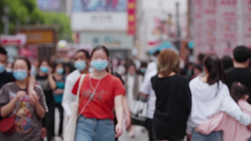 4k slow motion of blurred unrecognizable people wear face mask walking in the street city of Chengdu China crowd with mask during coronavirus Covid-19 pandemic outbreak