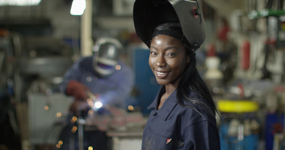 4K Portrait beautiful smiling female welder in metalwork shop. Slow motion. | Shutterstock HD Video #1051471279