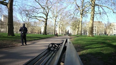 London, UK - January 2020: A man walks at a huge local park and stands to take a photo of the scenery. Downtown city. People sitting on benches in background.