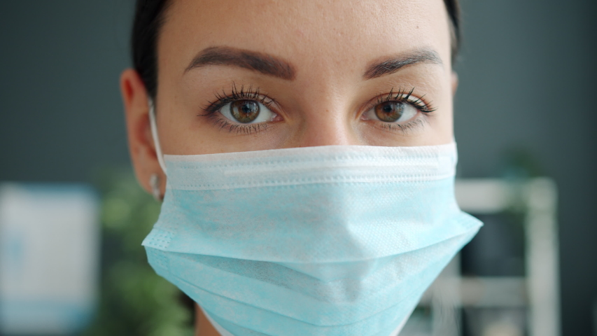 Portrait of beautiful young woman female doctor wearing medical face mask indoors in office. Medicine, people and infectious diseases concept. | Shutterstock HD Video #1051479541