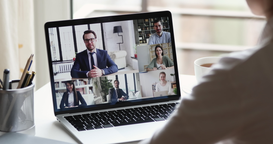 Webcam company team meeting concept. Remote employee conferencing boss and coworkers in online group virtual chat using pc video call app working from home office. Over shoulder laptop screen view #1051488613