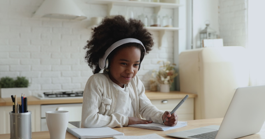 Cute african school girl elearning with online tutor at home. Mixed race child wearing headphones using computer app video calling watching online class lesson. Quarantine children education concept. | Shutterstock HD Video #1051507294