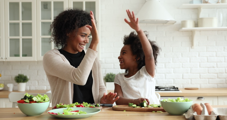 Happy african american family cute daughter and mum give high five having fun prepare healthy meal together. Smiling mixed race mother teaching kid learning cooking making vegetable salad in kitchen.