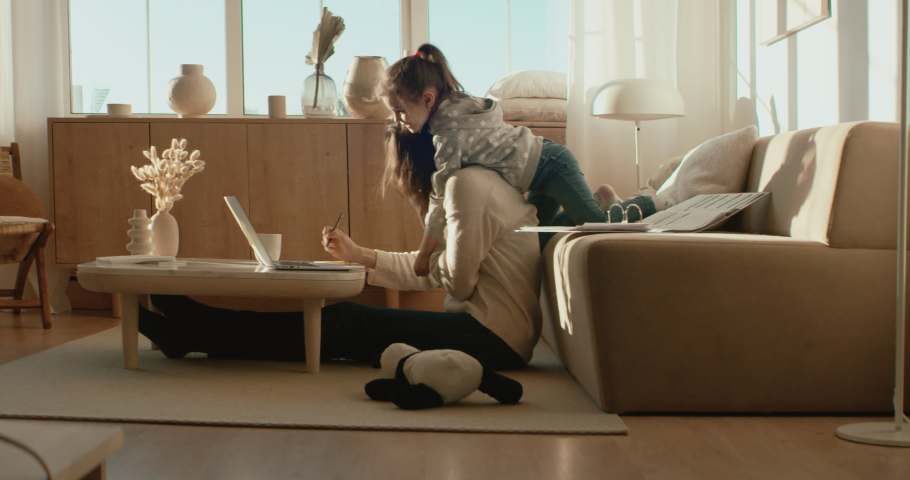 Mother working from home, having a phone call, while her daughter distracts her and drawing attention. Shot on RED Dragon | Shutterstock HD Video #1051515073