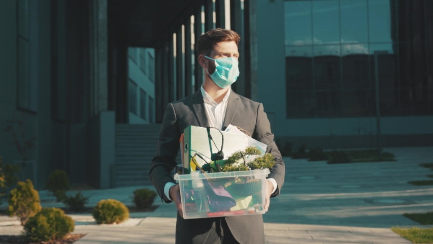 Man wear face mask walking with box of personal stuff got fired due to coronavirus crisis unemployed depression employment economy close up slow motion