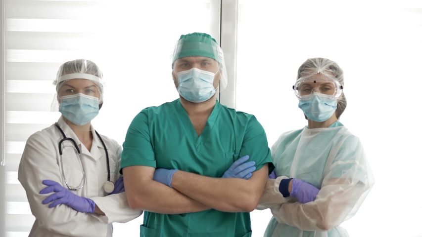 The Group of doctors in protective suits is ready to go. Looking at camera. Covid-19. | Shutterstock HD Video #1051522237