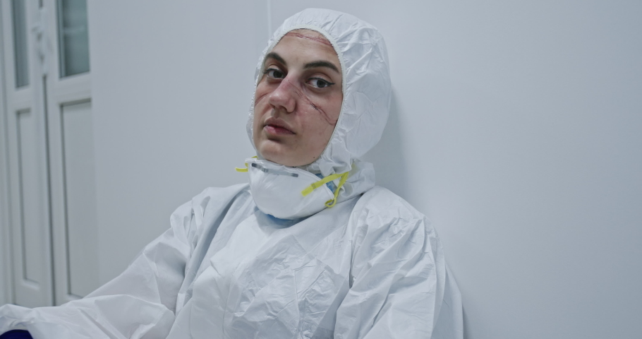 Exhausted doctor, nurse taking of coronavirus protective gear N95 mask uniform. Coronavirus Covid-19 outbrek.Mental state of medical professional.Face scars. Mask shortage. Overworked health workers | Shutterstock HD Video #1051523389