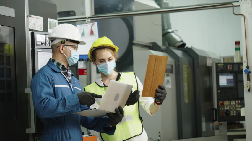 Factory engineer check machine equipment. Wear protective equipment. Safety helmet to prevent accidents. Mask to prevent dust or Coronavirus in operation Or industrial factories. Concept new normal. | Shutterstock HD Video #1051541869