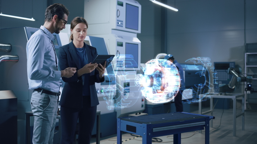 Factory Office Facility: Chief Engineer Holds Tablet Computer, Shows Augmented Reality Model of an Electric Generator to a Female Project Manager. Modern Industry 4.0 Research and Development Center.