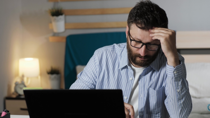 Tired man works at computer and writes notes in notebook. Bearded guy sits at desk in bedroom typing on laptop keyboard and takes notes in notebook. Work at home, freelance concept | Shutterstock HD Video #1051546219