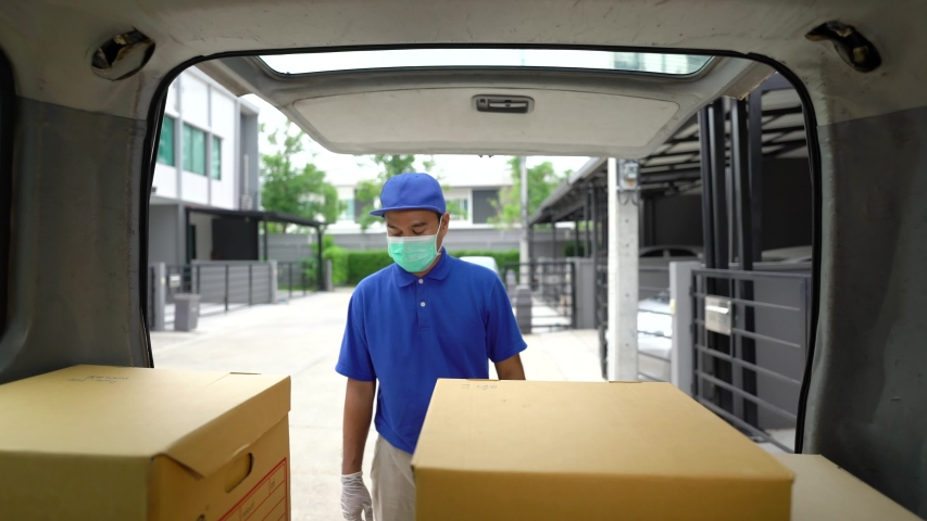 Corona Virus concept.Blue delivery handsome asian man wearing protection mask and medical rubber gloves puts cardboard boxes in the trunk of a car. Volunteer work in the midst of an epidemic.  | Shutterstock HD Video #1051546546