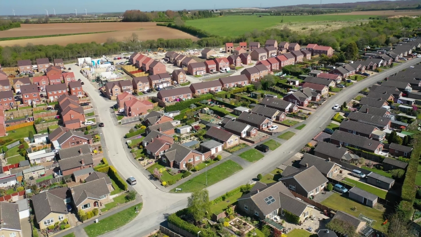 Aerial footage of a typical British housing  estate in the Village of Kippax in Leeds West Yorkshire, showing suburban housing estates, bungalows, road along side farmers fields the village.