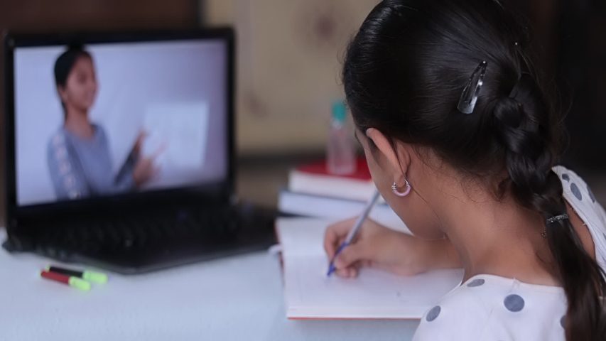 Concept of homeschooling or e-learning, young girl busy in writing by looking into laptop while teacher explaining during covid-19 or coronavirus pandemic crisis.   Shutterstock HD Video #1051556461