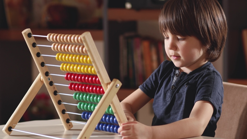 4K,Little boy working with abacus in home.