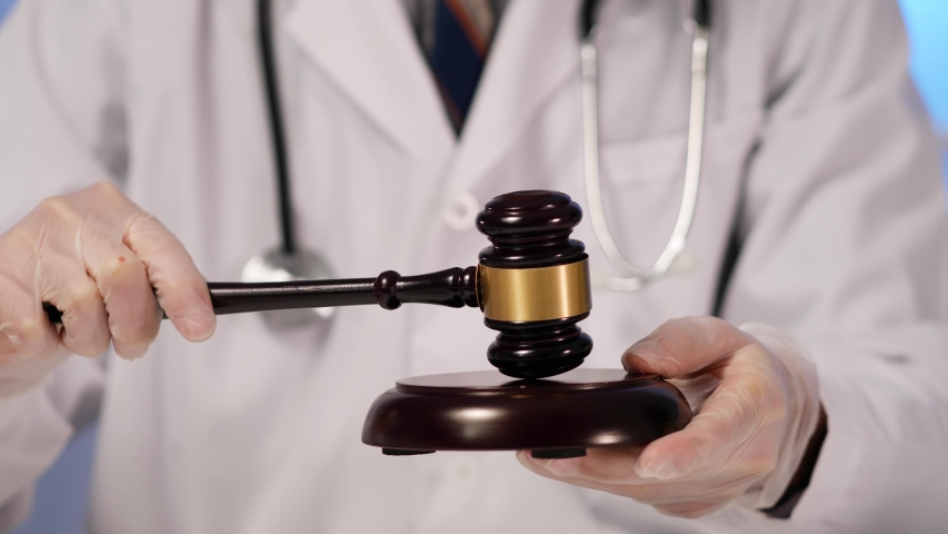 Closeup on a professional medical doctor, wearing a white lab coat and a stethoscope and protective gloves , holding a hammer and gavel to practise law   Shutterstock HD Video #1051568098