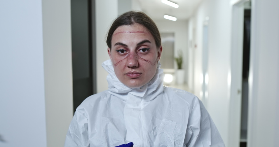 Nurse or doctor in protective clothing with her goggles and face mask removed looking at camera in hospital before turning to walk away during the Covid-19 coronavirus pandemic. | Shutterstock HD Video #1051585687