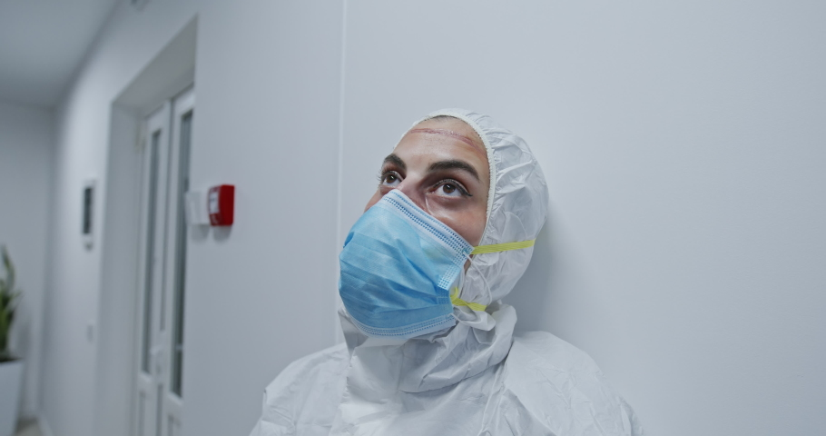 Dramatic video portrait of an exhausted nurse or physician praying while taking off the protection surgical face mask in the hospital during Covid-19 pandemia. Nurse taking off the face mask during Royalty-Free Stock Footage #1051585708