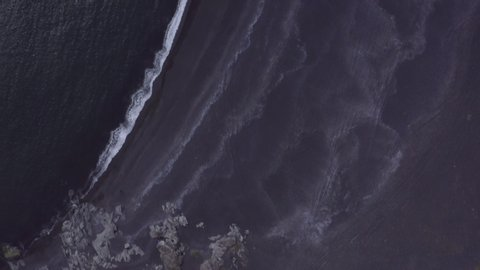 Aerial shot of waves rushing at sea shore on beach, drone flying forwards over coast - Southwestern Iceland, Iceland