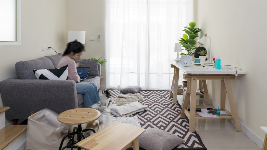 Timelapse of asian woman with pet set up room for work from home in quarantine social distance work remotely concept. New home office setup, cleaning, housework in new normal or next normal asia life. Royalty-Free Stock Footage #1051594963