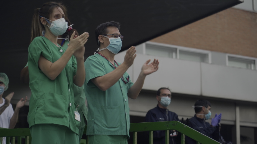 MADRID, SPAIN - APRIL 4 2020. Medical staff from 12 de Octubre hospital who are fighting coronavirus applaud back the people of Madrid and police officers for their support