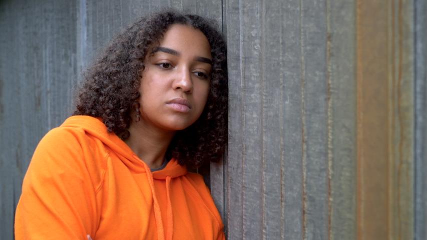 Beautiful mixed race African American girl teenager young woman looking sad wearing an orange hoodie in an urban city environment