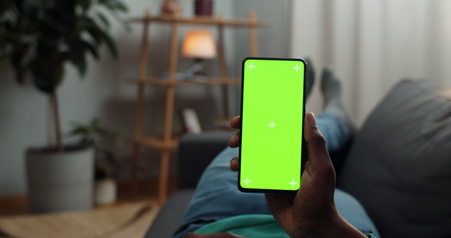 Young man lying on couch with modern smartphone in his hand while looking on mock up screen with trecking markers on it. Concept of green screen and chroma key. Cosy home background Royalty-Free Stock Footage #1051618927