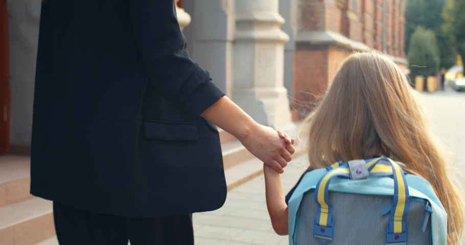 Close up view of little blond girl in uniform with bag walking with her mother hand in hand. Backside view of child holding her mom and entering in school early morning. Outdoors | Shutterstock HD Video #1051618948