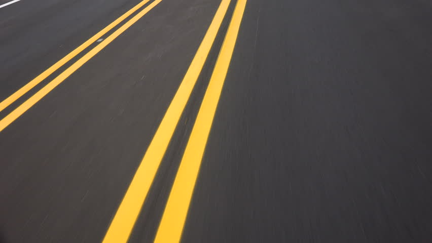 Driving on newly paved road, double yellow lines converge, close up, driver POV. 4K UHD 3840x2160 | Shutterstock HD Video #10516220