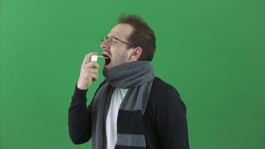 A man is sick, throat, cough, allergy. Takes medicine in throat spray. A scarf around the neck. Respiratory disease, virus. On a green background, chromakey | Shutterstock HD Video #1051622641
