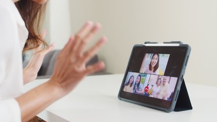 Young Asian business female using tablet video call talking with family while working from home at living room. Self-isolation, social distancing, quarantine for coronavirus in next normal concept.