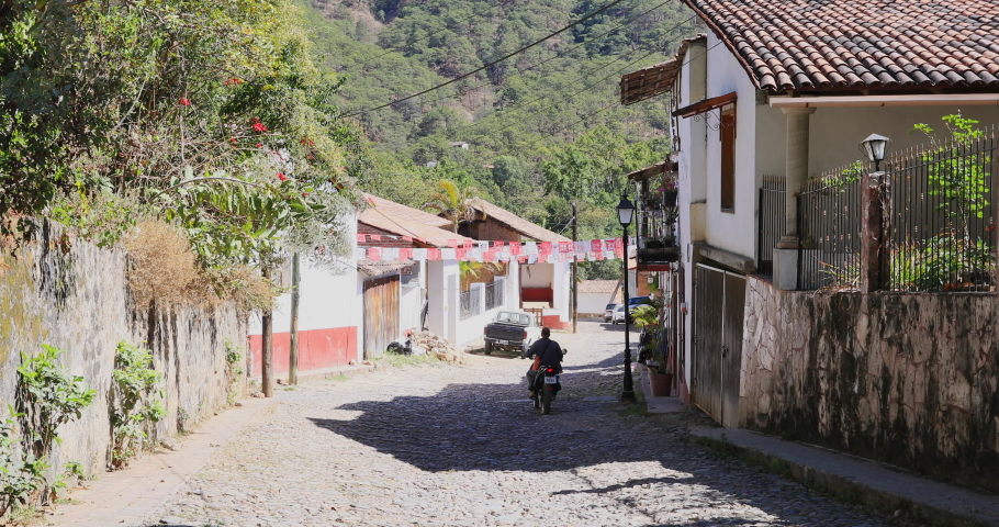 SAN SEBASTIAN, MEXICO - 9 APR 2019: San Sebastian del Oeste Mexico men motorcycles cobblestone. Town and municipality in Jalisco state. Historical tourism destination. Old haciendas and historic home. Royalty-Free Stock Footage #1051641715