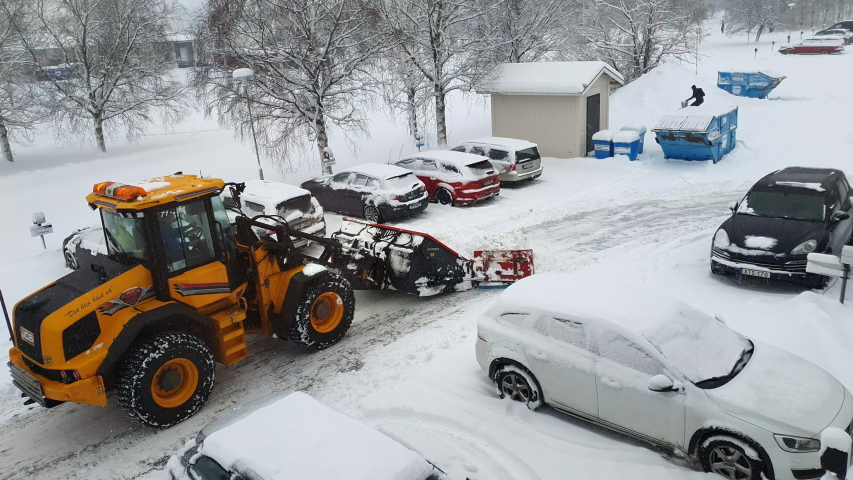 UMEA, SWEDEN - JANUARY 30, 2020: Big orange yellow tractor plowing snow close to parked car which was going to start, parking lot with parked cars, trees are covered by snow. Scandinavian weather