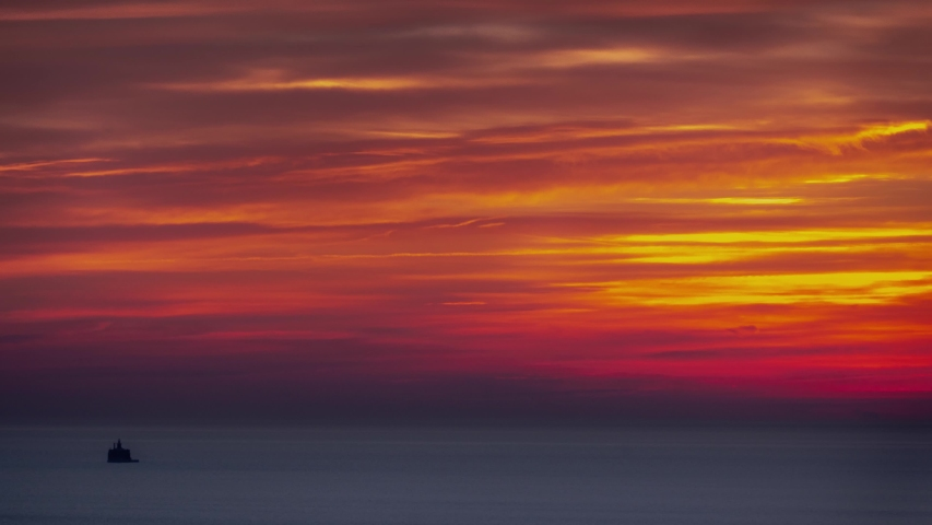 Aerial timelapse of an incredible beautiful layered feathery pink, orange, blue and yellow sky sunrise over the calm rippling water of Lake Michigan in Chicago.