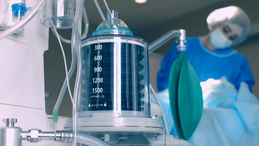 The operation of the ventilator piston, against the background of a doctor caring for a ballroom in a coma. Patient in the ward on an apparatus for cold ventilation in pneumonia. Ward with the patient Royalty-Free Stock Footage #1051642165