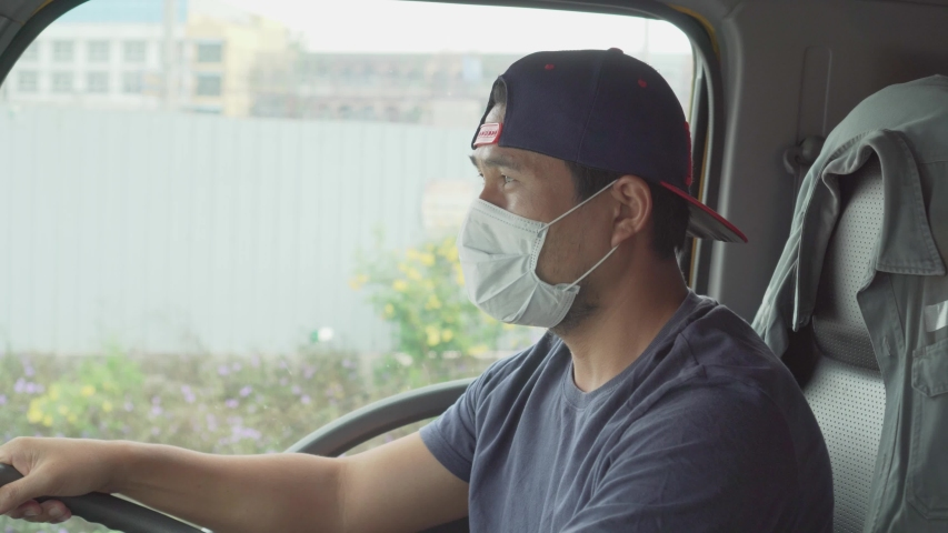 Asian truck drivers wearing masks to protect against dust and the spread of COVID 19 in front of the car. Safety ideas for a worker in the transportation business. And is a new normal life.