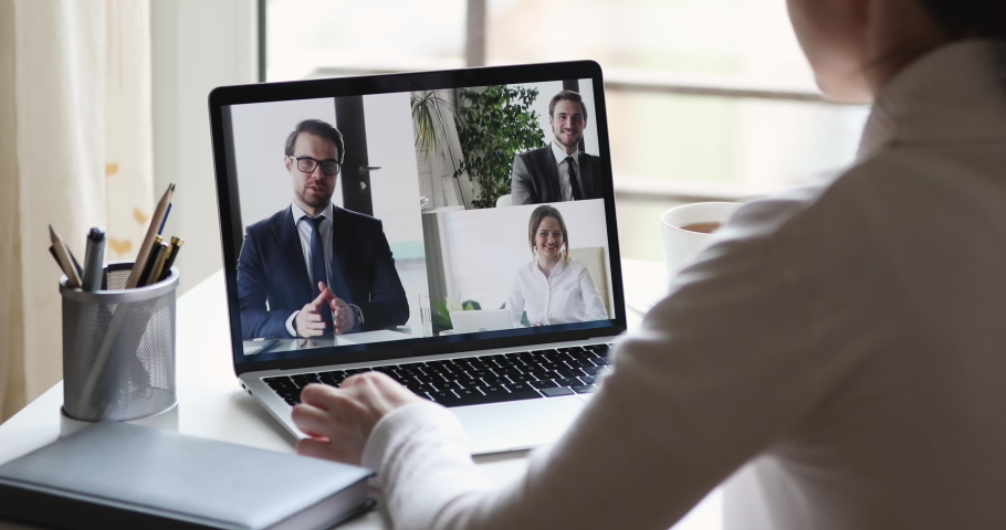 Over shoulder closeup view of business woman videoconferencing partners team by online video call virtual app. Remote worker conferencing colleagues group on pc laptop screen working from home office.