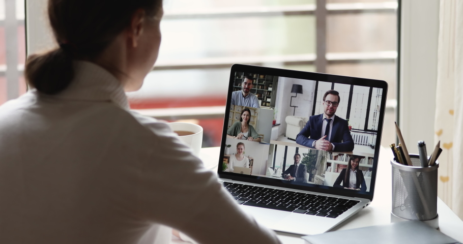 Female office worker working from home video conferencing businesspeople group communicate during virtual web cam meeting. Remote videoconference call concept. Over shoulder closeup laptop screen view | Shutterstock HD Video #1051686103