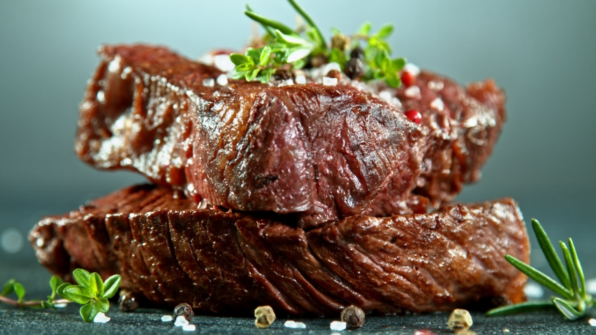 Close-up of falling tasty beef steak, super slow motion, filmed on high speed cinematic camera at 1000 fps. Royalty-Free Stock Footage #1051687072