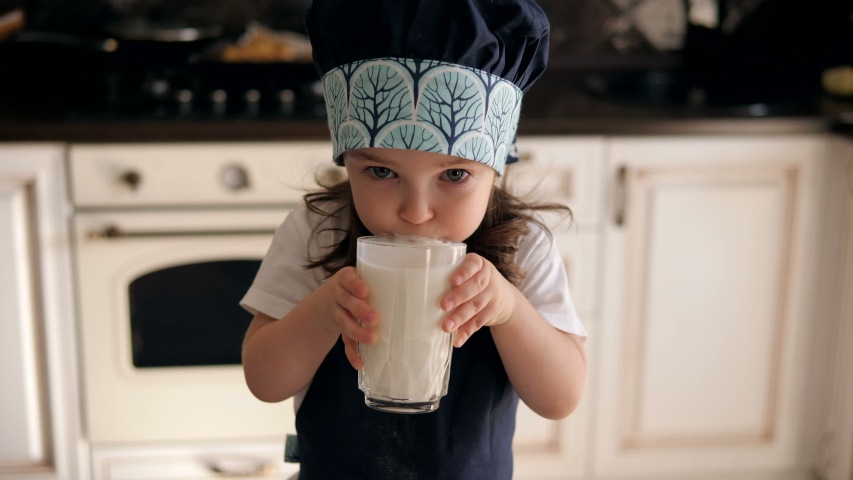 Portrait of a little three-year-old girl in an apron and cap in the kitchen, she drinks kefir or milk and leaves a milky moustache on her lips. There are Christmas cookies on the table.