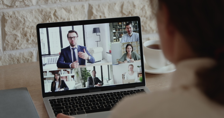 Over shoulder closeup view of remote employee conferencing in online group virtual chat on laptop screen. Company staff colleagues and boss using pc video call app working from home office by web cam. | Shutterstock HD Video #1051691221