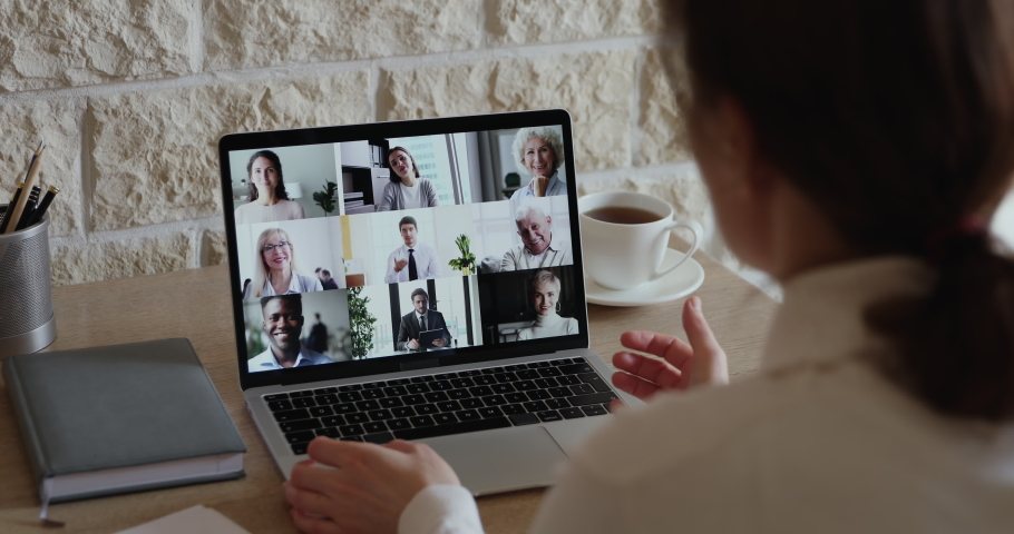 Over shoulder view of businesswoman video conferencing diverse business people team on laptop screen engaged in online group call, virtual corporate meeting using pc app for distance company teamwork. Royalty-Free Stock Footage #1051691224