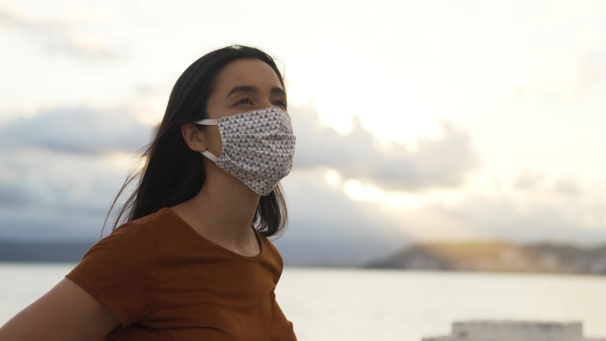 Hopeful Young woman takes off medical mask. Female breathes deeply and smiling. Corona virus due quarantine fatigue