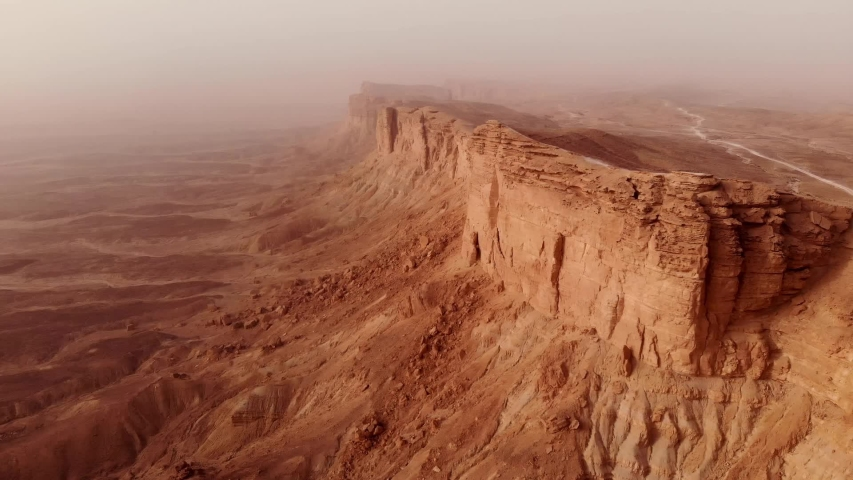 Aerial of The Edge of the World (Jebel Fihrayn) is an unexpected and dramatic geological wonder in the rocky desert northwest of Riyadh, Saudi Arabia | Shutterstock HD Video #1051698598