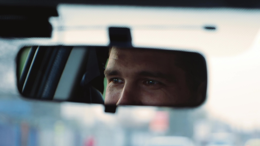 Young man inside car. Happy positive caucasian man driving car fast and look at rear view mirror with smile. Blurred background. Slow motion. | Shutterstock HD Video #1051699021