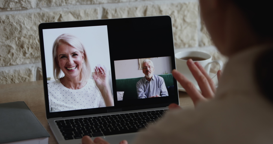 Young woman daughter video calling senior old parents by web cam having distance online conversation, virtual conference chat using videocall application on laptop. Over shoulder closeup screen view.
